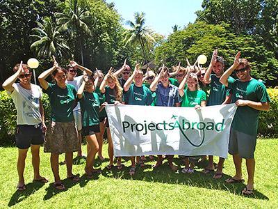 斐濟鯊魚保育項目志工團隊手持Projects Abroad旗幟在工作地方留念