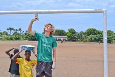 加納兒童幫助參與建設項目的國際志工塗漆,粉飾球場龍門