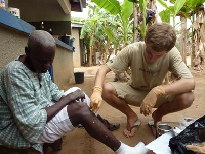 A volunteer check on the progress of a patient's leg at a leprosy camp in Ghana