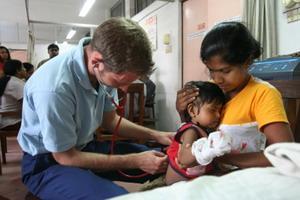 醫療及保健志工在亞洲檢查嬰兒的身體