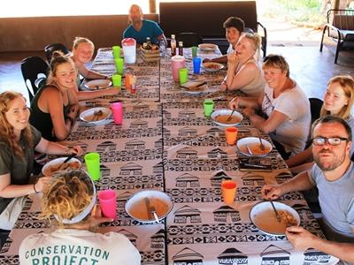 一群Projects Abroad環境保護項目志工在他們博茨瓦納的Wild at Tuli生態保護區宿舍享用飯餐