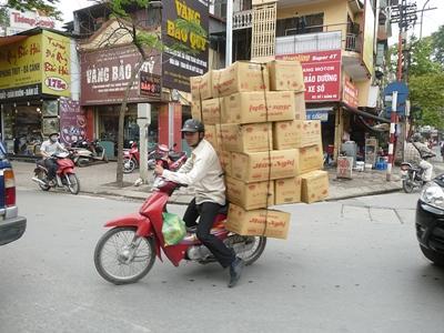 越南本地人騎著電單車背上運載盒子