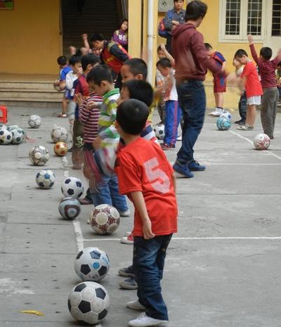 東南亞孩子們在學校與體育教練志工一起訓練踢足球的技術