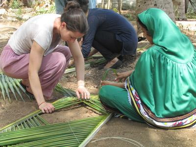 Volunteer arranging a palm tree structure in a local community with Projects Abroad