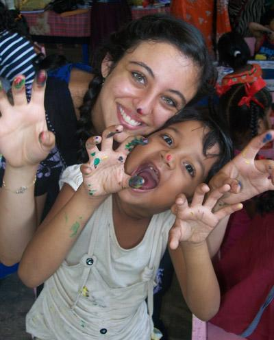 Volunteer and child play with finger paint on a Care placement in Sri Lanka
