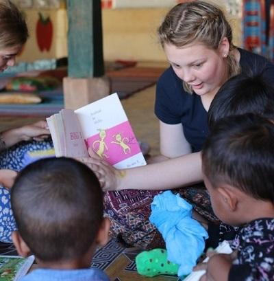 參與社區關愛的學生志工在柬埔寨教孩子們閱讀認字