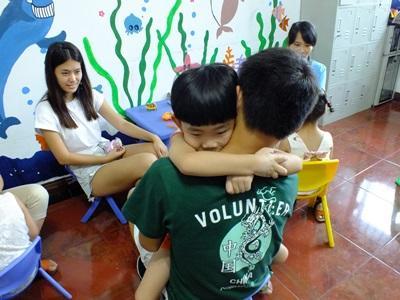 一名中國孩子由Projects Abroad志工抱著