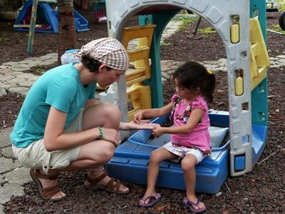 志工在厄瓜多爾幼兒園的遊樂場與年輕女孩玩遊戲