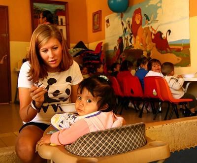 志工在墨西哥關愛中心幫忙照顧年幼女孩的飲食