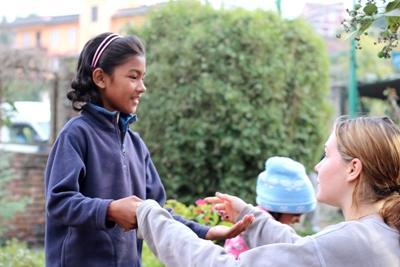一名尼泊爾女孩投入跟志工玩拍掌遊戲