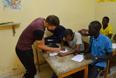 Projects Abroad志工在非洲塞內加爾幫助一群街童指導他們完成家課作業