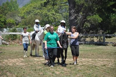 南非志工在馬術治療項目中幫助一群身心障礙兒童。
