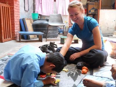尼泊爾兒童在志工幫助下努力完成一幅砌圖