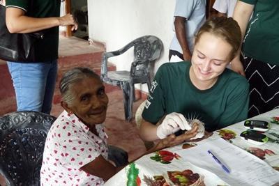 高中生志工檢查斯里蘭卡一名婦女的血糖指數