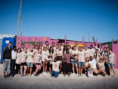 高中生志工團隊在國外合力完成一所學校的外牆粉飾工作。