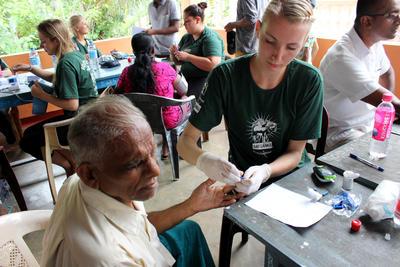 醫療外展工作,一名女志工幫一名斯里蘭卡男生量度血壓及血糖水平