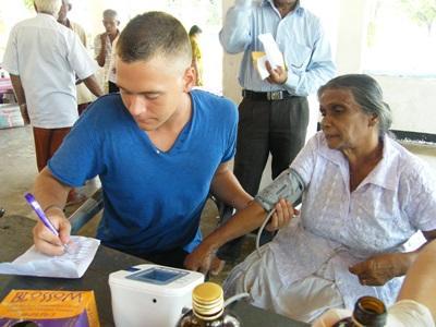 護理實習生參與斯里蘭卡的外展醫療活動,紀錄一名老婦的血壓