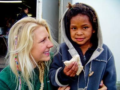 一名女實習生在南非黑人城鎮區域工作,看著孩子吃麵包