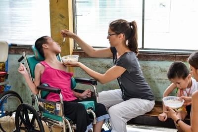 Projects Abroad實習生參與越南的職業治療項目在服務機構幫助身心障礙兒童吃午飯