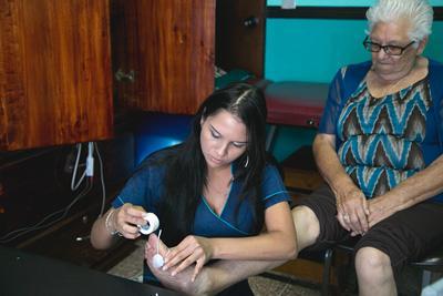 物理治療實習生正在幫助哥斯達黎加一名年長婦人進行治療