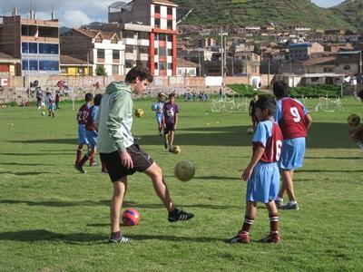 秘魯兒童參與足球訓練,看著Projects Abroad志工學習踢球技巧