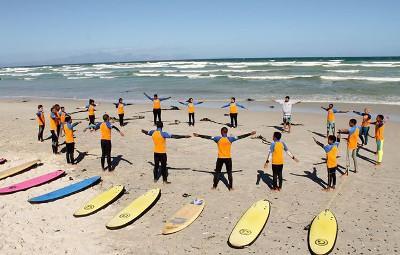 在南非的開普敦,弱勢兒童與衝浪項目志工站在一起做伸展熱身