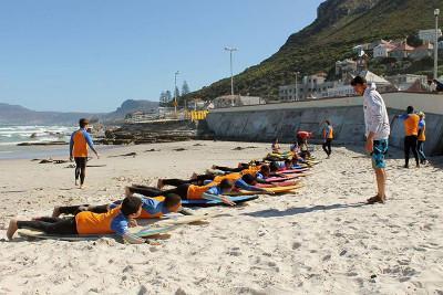 一群兒童在Muizenberg海灘專心上衝浪課,課堂是由志工帶領