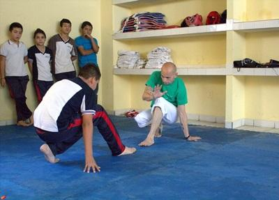 Volunteer coach demonstrates sports skills to children in Mexico