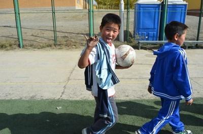 蒙古男童在志工指導下練習踢足球技巧