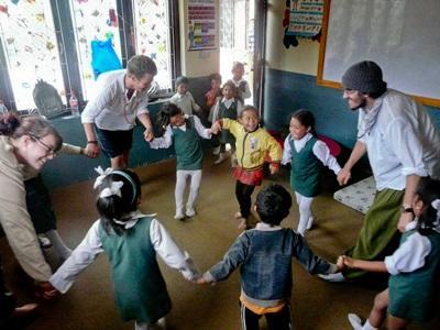 三名志工在課堂帶領一群尼泊爾學童去學習