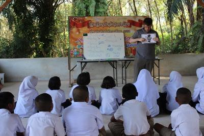 一群兒童在教學志工負責的英語課上專注聆聽老師的講解