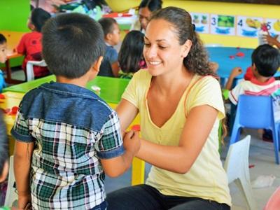 菲律賓學校的學生得到女志工教師的幫助