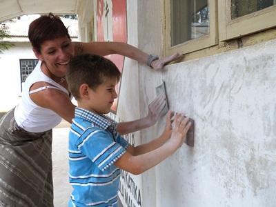 母親和孩子一起參與Projects Abroad的志工項目,幫忙粉刷建築物的外牆